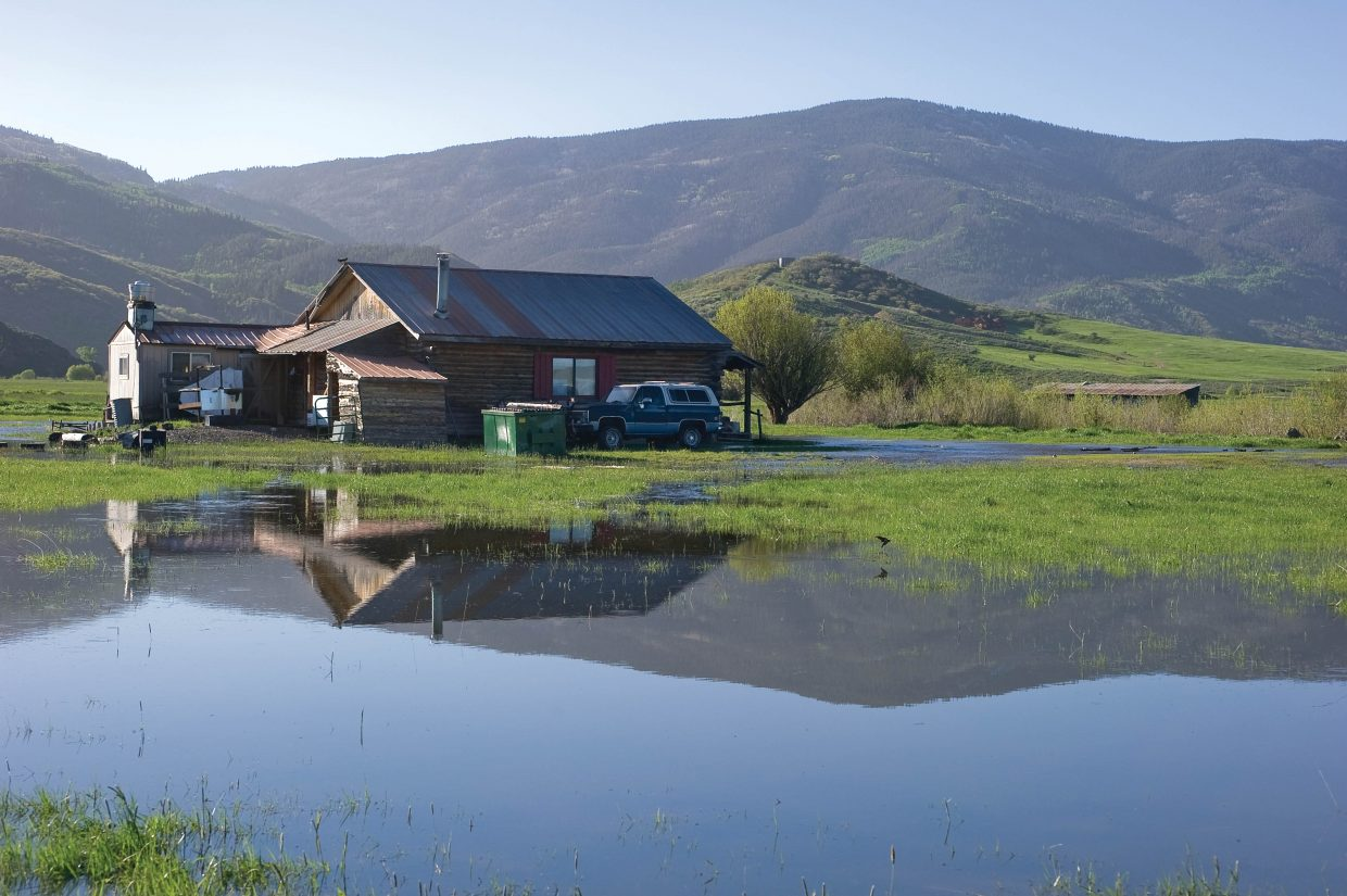 A small cabin on the banks of the Yampa River south of Steamboat Springs is surrounded by water Tuesday morning as runoff continues to push the swelling Yampa River past its banks with spring runoff.