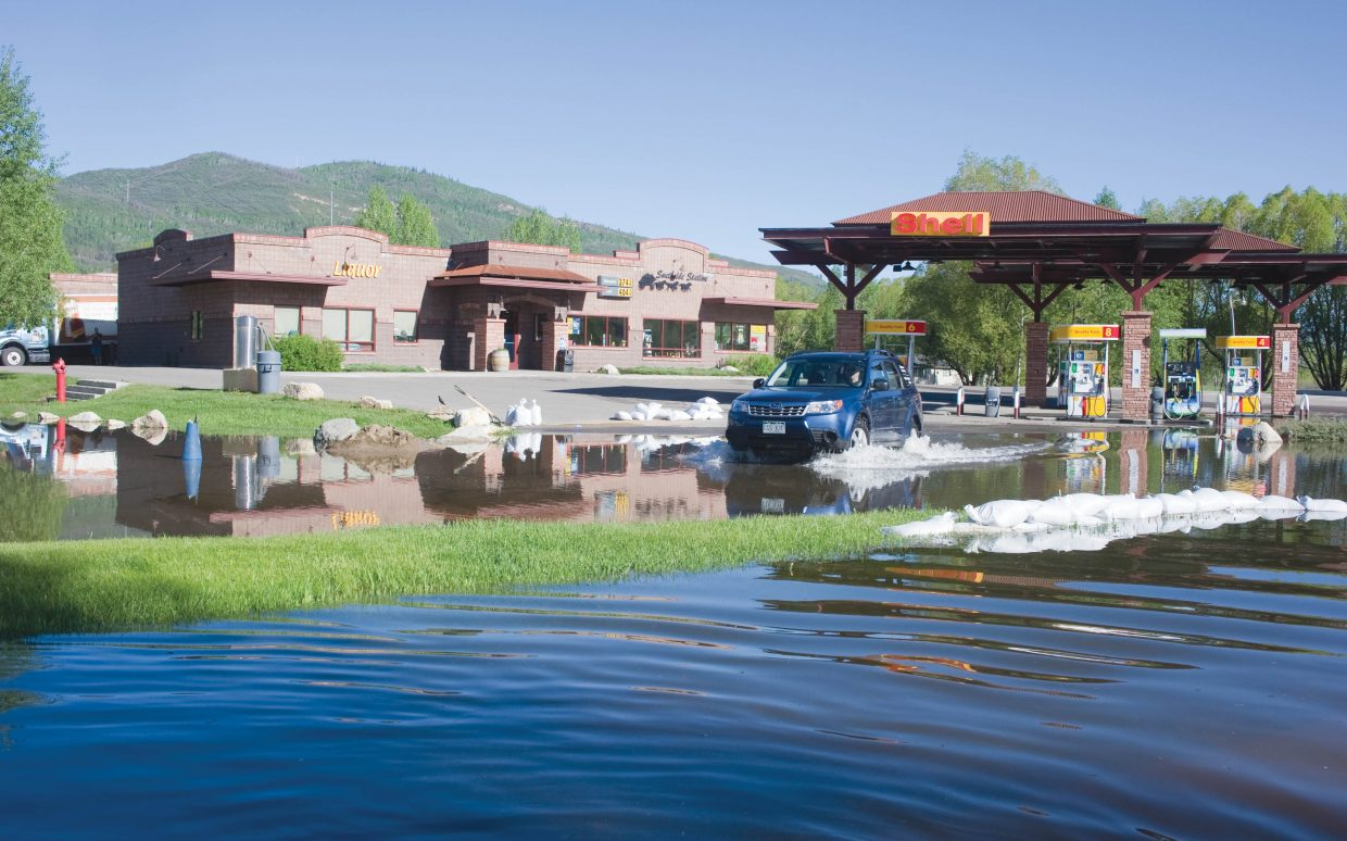 Water from Walton Creek and the Yampa River is starting to reach the parking lot at the Southside Station on the south side of Steamboat Springs. The water has overrun sandbags lined along the bike path Tuesday and started to fill into the parking lot of the business, which is still open.