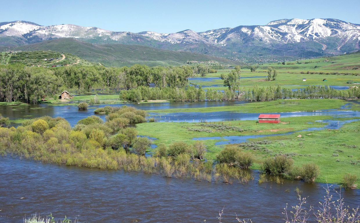 The Yampa River continues to plot its own course through ranch land west of Steamboat Springs. Judging from the amount of snow still visible on the surrounding peaks and the slopes of Steamboat Ski Area on Wednesday afternoon, the river could be running full for some time to come.