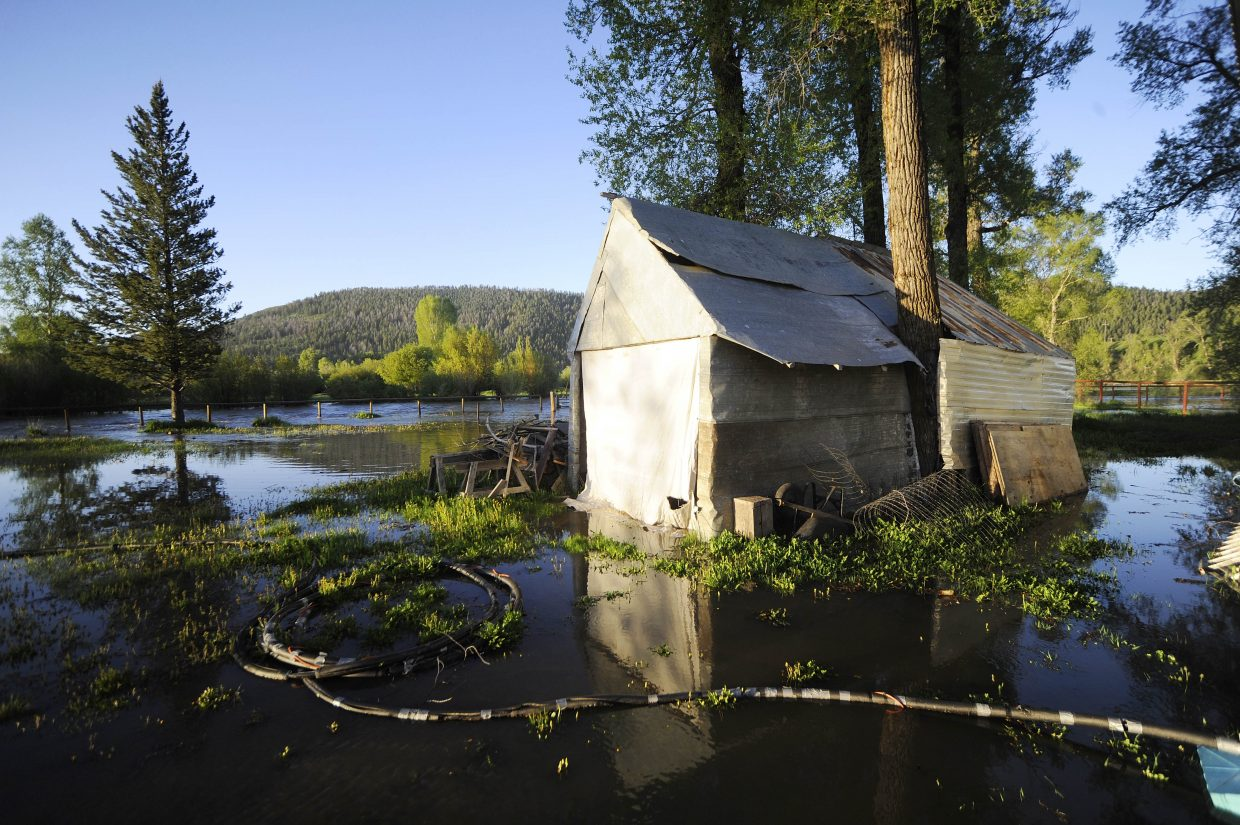 Water surrounds a shed Tuesday on Connie Fry's property along Routt County Road 44.