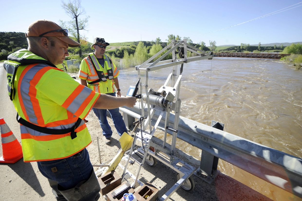 U.S. Geological Survey hydrologic technicians Mark Henneberg, left, and Michael Gustafson measure the flow of the Elk River on Tuesday morning.