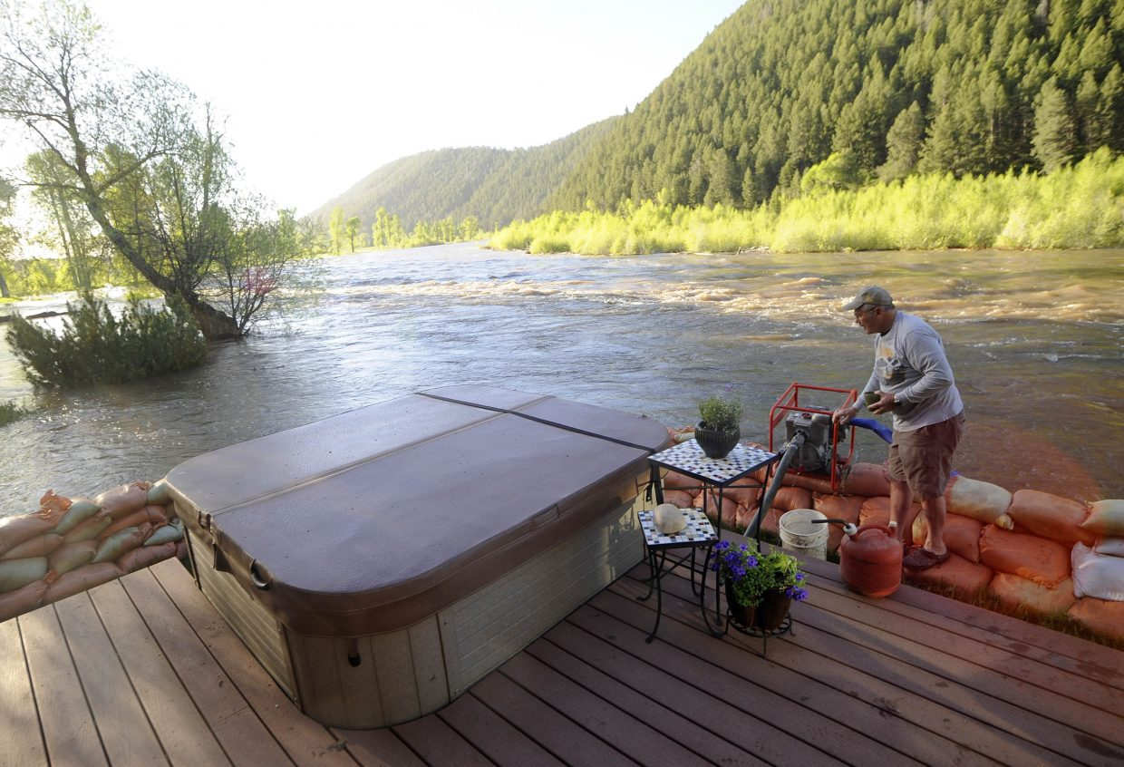 Kent Osteen checks on a pump Tuesday morning at his home along the Yampa River.