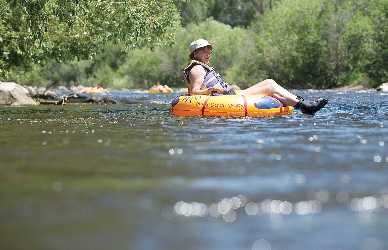 Jennifer Lane enjoys the cool waters of the Yampa River on Friday afternoon while tubing through Steamboat Springs.