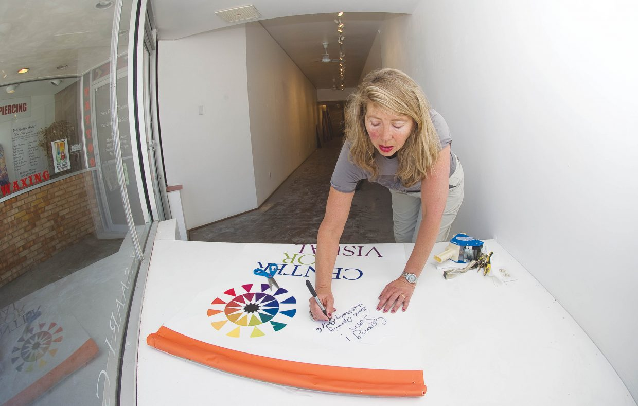 Linda Laughlin, executive director of the nonprofit Steamboat Springs Center for Visual Arts, works on a sign Friday that details the gallery's reopening in a new space at 837 Lincoln Ave. Currently located at 906 Lincoln Ave., the Center for Visual Arts is a 3-year-old collaborative gallery that aims to foster the visual arts community through providing a space for local artists and through outreach and mentoring programs. Laughlin and a team of builders will be renovating the new space by adding and taking down dividing walls, laying carpet and building a small kitchen and customer service space. The grand opening will be at First Friday Artwalk on July 6. In addition, artist workshops with MB Warner will begin July 2 along with a new program called First Monday Critiques, which is open to all artists.