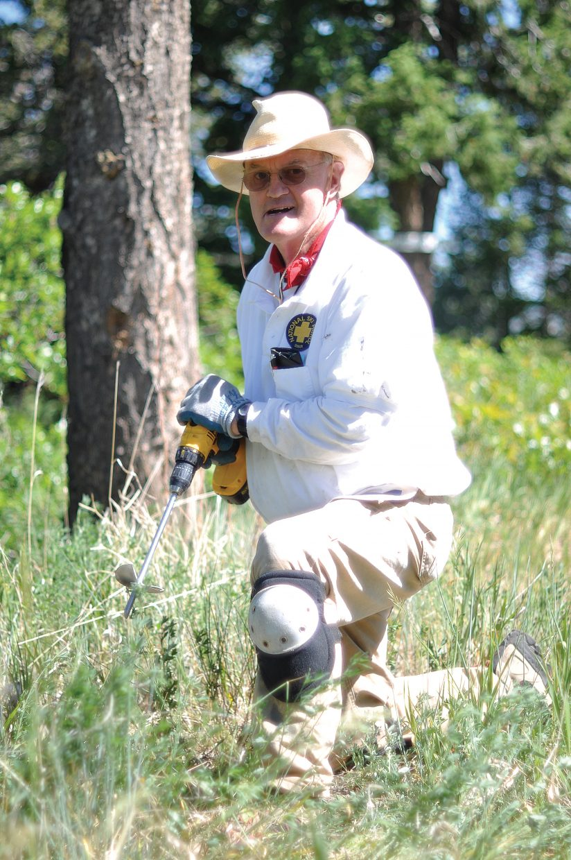 Steamboat Springs resident Frank Dolman uses a drill with an auger attachment Saturday to quickly create holes for planting baby trees in the rock-filled surface of Howelsen Hill as part of ReTree Steamboat 2012.