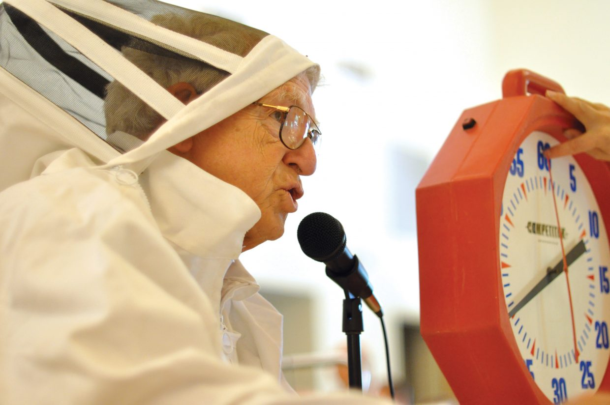 Dressed in a beekeeper suit, Bud Romberg pronounces a word for competing teams at Saturday's Community Spelling Bee.