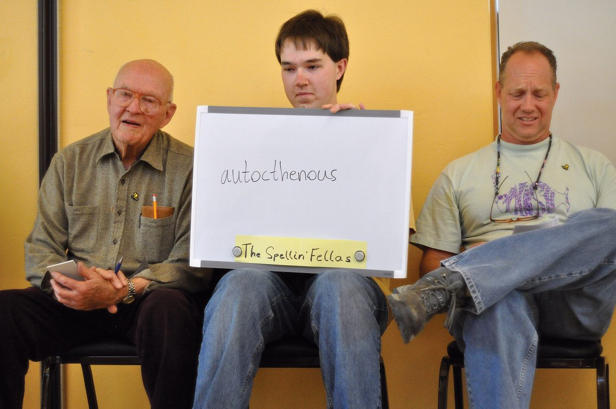 The Spellin' Fellas, from left, Gene Cook, Zach Schmidt and Mike Schmidt display their submission for the word autochthonous Saturday at the Community Spelling Bee. The team previously had challenged the spelling of a word that knocked it out of the preliminary round, and the challenge proved successful as spelling bee organizers decided to redo the round.