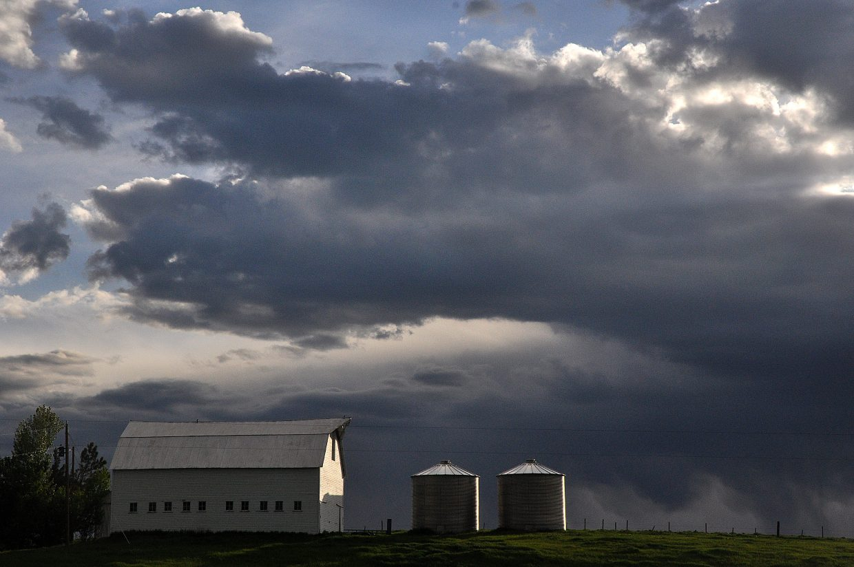 The last rays of light Friday highlight a barn and silos west of Steamboat Springs as storms approach in the distance.
