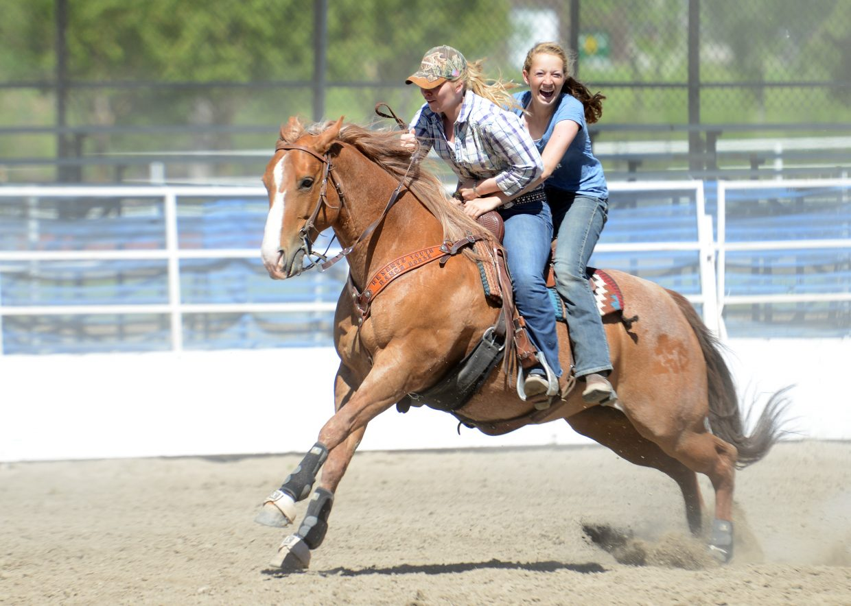 """Zava Zupan, right, hangs on as MacKenzie Holmberg tries to guide their horse across the finish line during the cowboy rescue event at a ranch rodeo Sunday in Steamboat Springs. The event drew about a dozen competitors, casting them against one another in various horse and rope events. The South Routt Cowboys, with Madison George, Morgan Goerge, Joe Schalnus and Taylore Schalnus, emerged atop the standings. """"It was a blast,"""" Joe Schalnus said. """"Sure beat a day of work."""""""