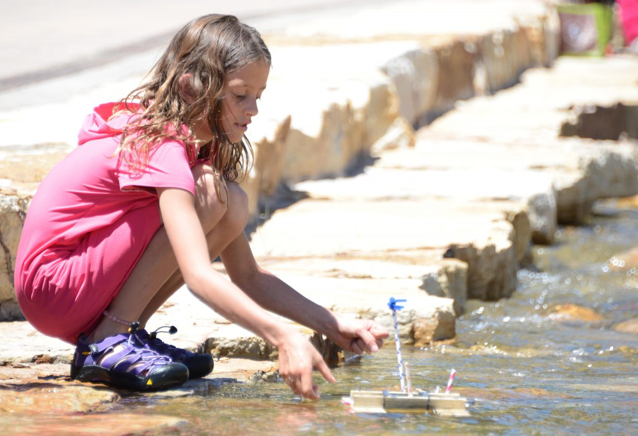 Tori Bilbrey, 9, lets loose in Burgess Creek the boat she made from beetle-killed wood at a sustainability expo that capped Sunday's ReTree Steamboat event. Volunteers for the event planted trees across Steamboat Springs, including many on the slopes of Steamboat Ski Area.