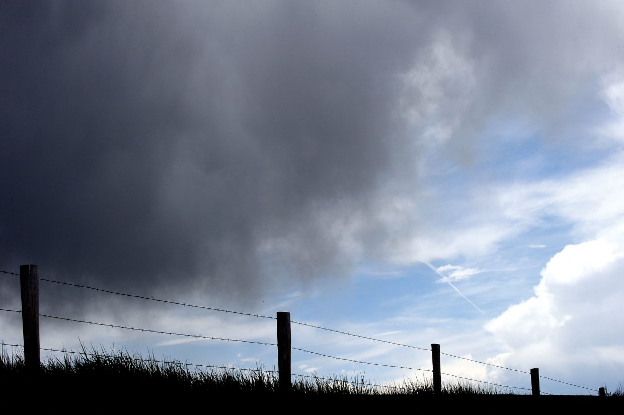 Storm clouds build over a fence line along Routt County Road 33.