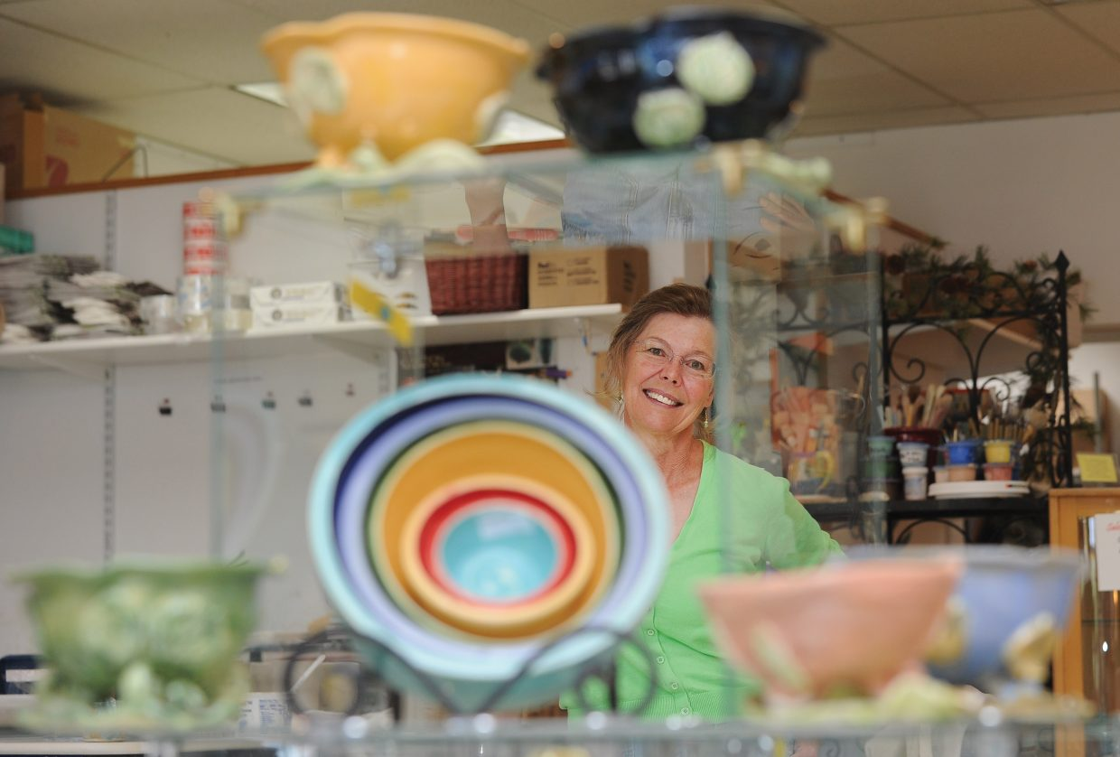 Local artist Deb Babcock stands behind a display stand inside Blue Sky Pottery, the shop she owns in Steamboat Springs. Babcock has been the subject of several magazine articles and is gaining a strong following on the Internet.