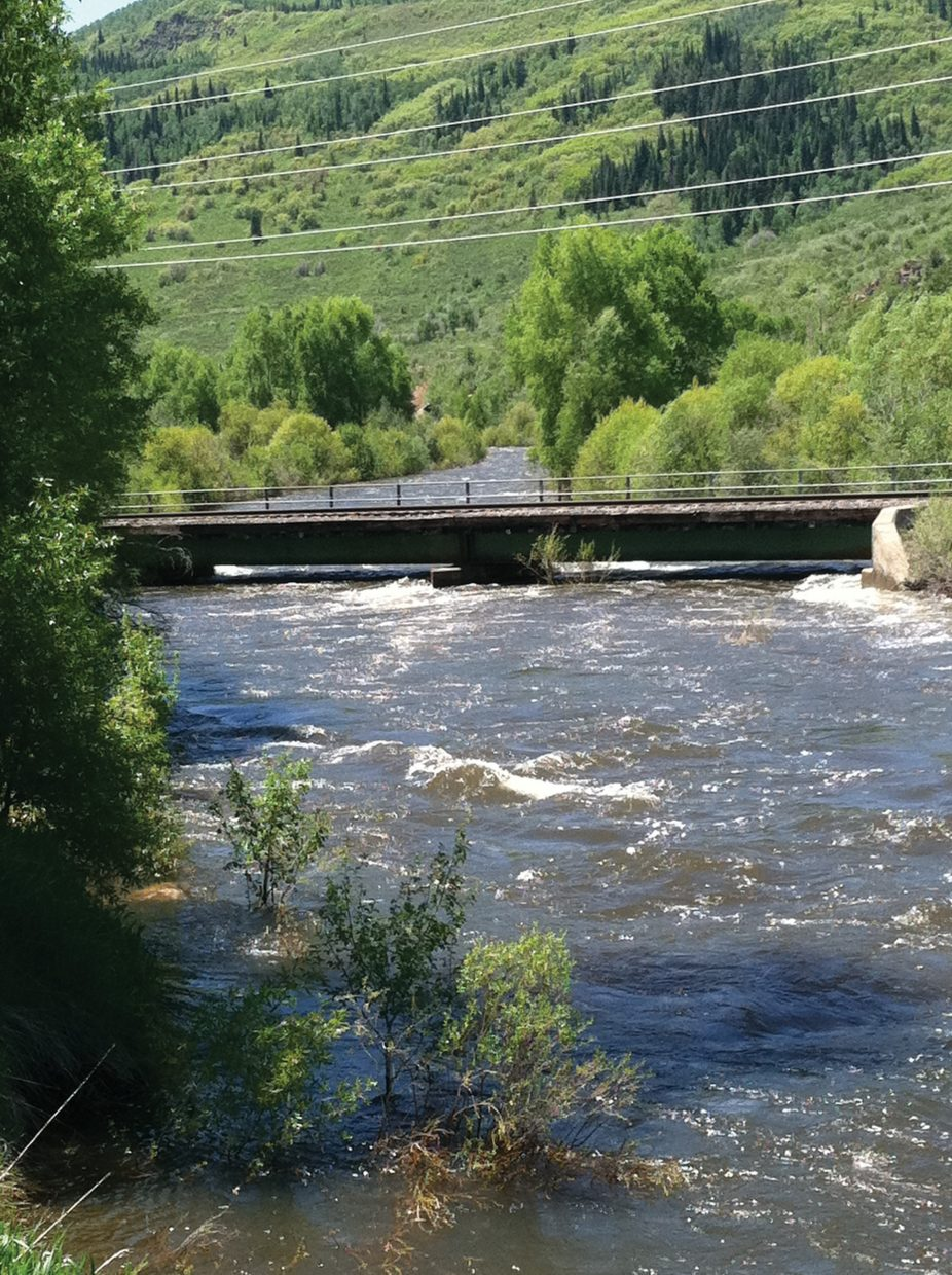 A swollen Yampa River just clears the bottom of a railroad bridge in Steamboat Springs on Sunday, June 12.