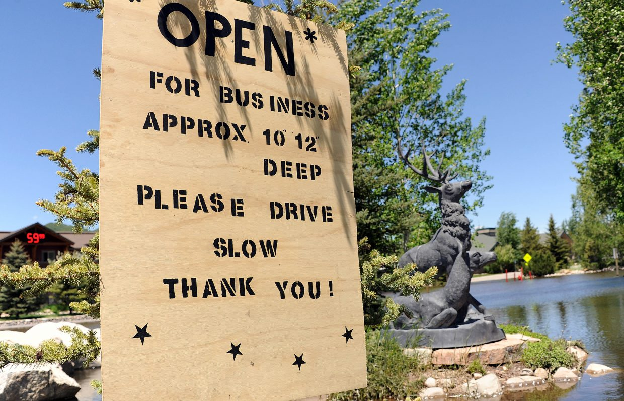 A sign in front Steamboat Hotel encourages customers to drive through the flood waters that have been in front of the hotel for the past couple of weeks.