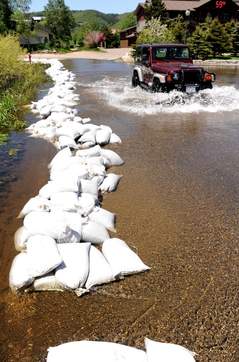 A Jeep charges through flood waters in front of Steamboat Hotel on Sunday in Steamboat Springs.
