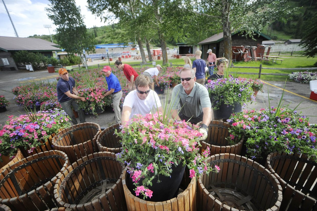 Rotary Club of Steamboat Springs members Dennis Podzemny, right, and David Wittlinger load flowers into a barrel Tuesday afternoon at Howelsen Hill. Flowers were distributed to locations throughout town as part of a Rotary Club fundraiser. More flowers are available and can be purchased by emailing Karl@steamboatlakemarina.com.