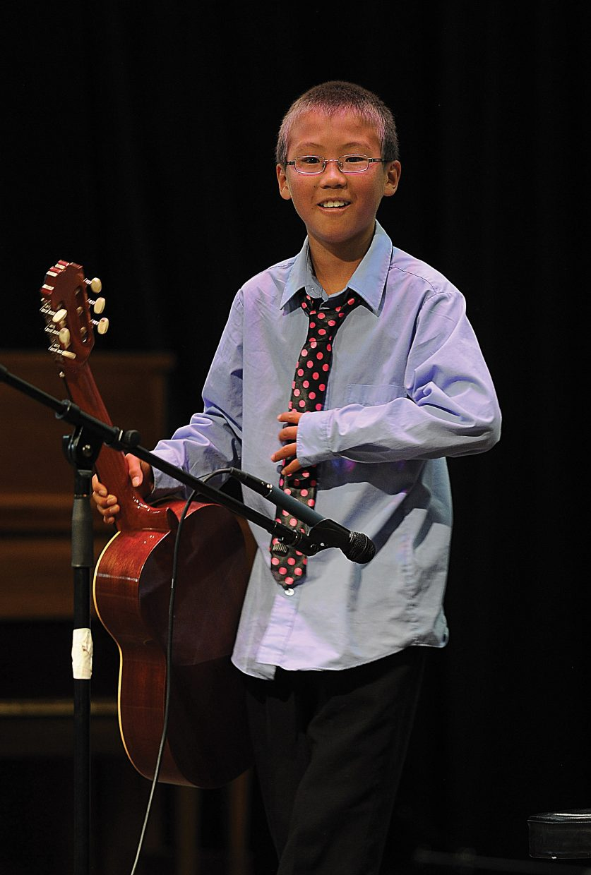 """Soda Creek Elementary School fifth-grader James Berntsen smiles onstage after performing """"Allegro"""" on his guitar Wednesday morning as part of a talent show at the school."""