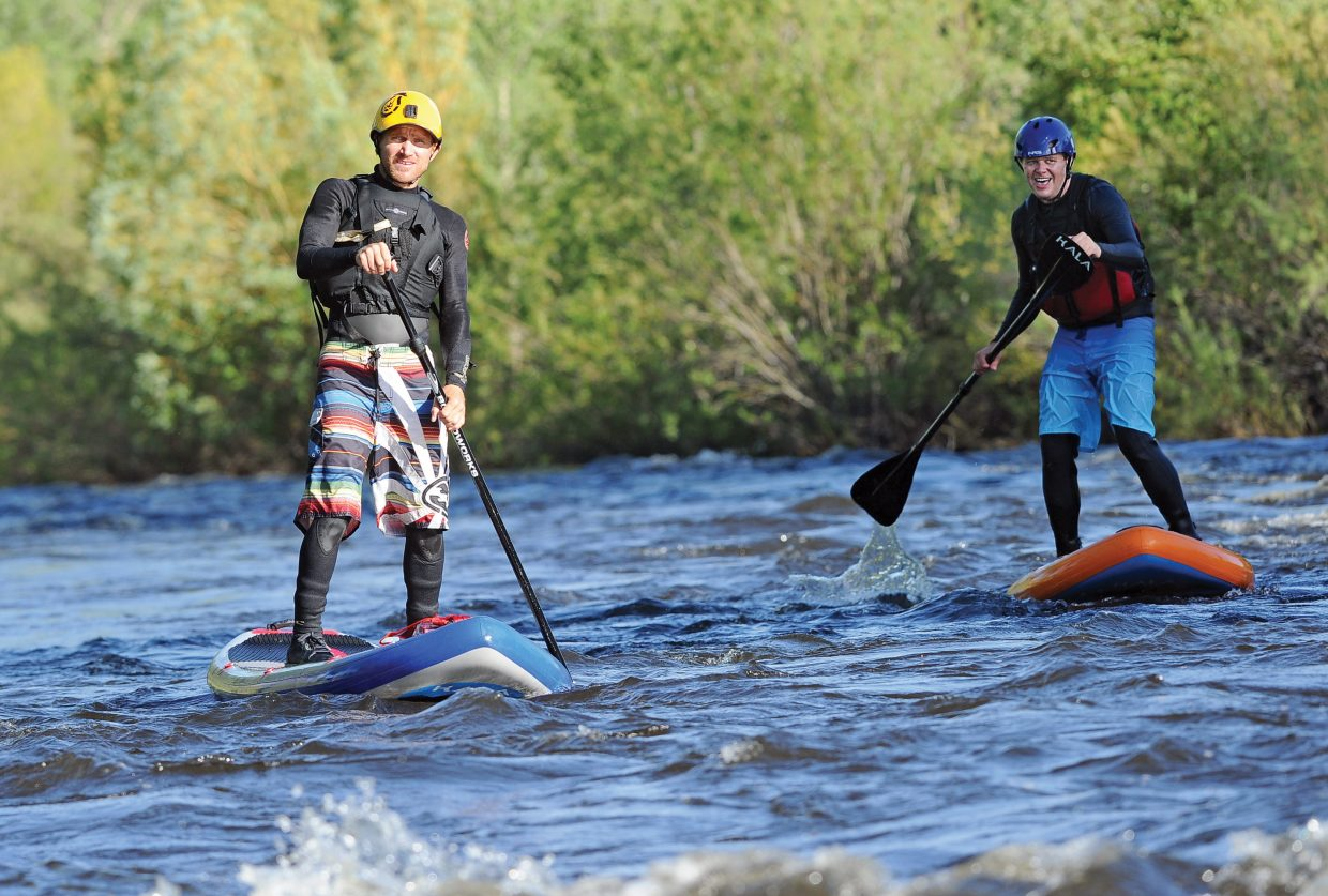 Steamboat Today reporter Joel Reichenberger, right, learns from Danny Tebbenkamp, of Steamboat Paddleboard Adventures, how to stand-up paddleboard on the Yampa River. Stand-up paddleboarding has swept into Steamboat Springs, proving a highlight of the Yampa River Festival and is the newest, fastest growing attraction on the river.