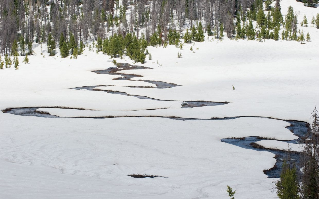 A stream cuts through a snowfield at the top of Rabbit Ears Pass on Monday. Warmer weather has taken a toll on snowpack at higher elevations during the past week.