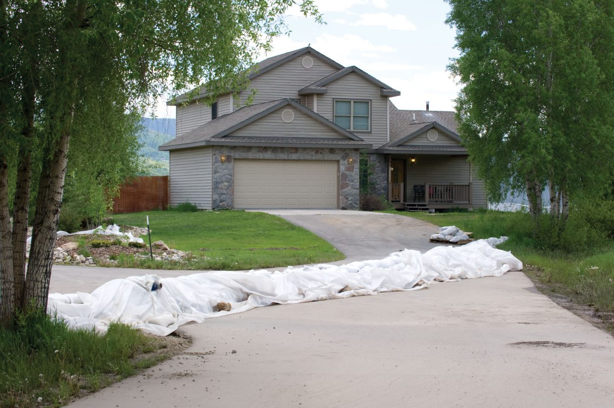 Sandbags still stand in front of the parsonage at Steamboat Christian Center on Monday afternoon. The bags were placed in front of the home last week to divert floodwater, which used to surround the home, to a nearby field.