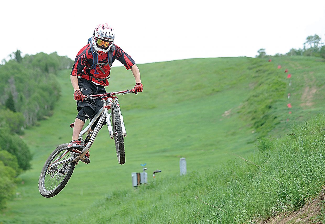 Stephen Wilson hits a series of rollers Thursday along a downhill track near the base of Steamboat Ski Area. The gondola, Bike Park and many of the trails were scheduled to open as part of Sponsorship Day on Thursday, but high winds led officials to postpone the fundraiser for Routt County Riders. The Bike Park is expected to open for the season Friday.