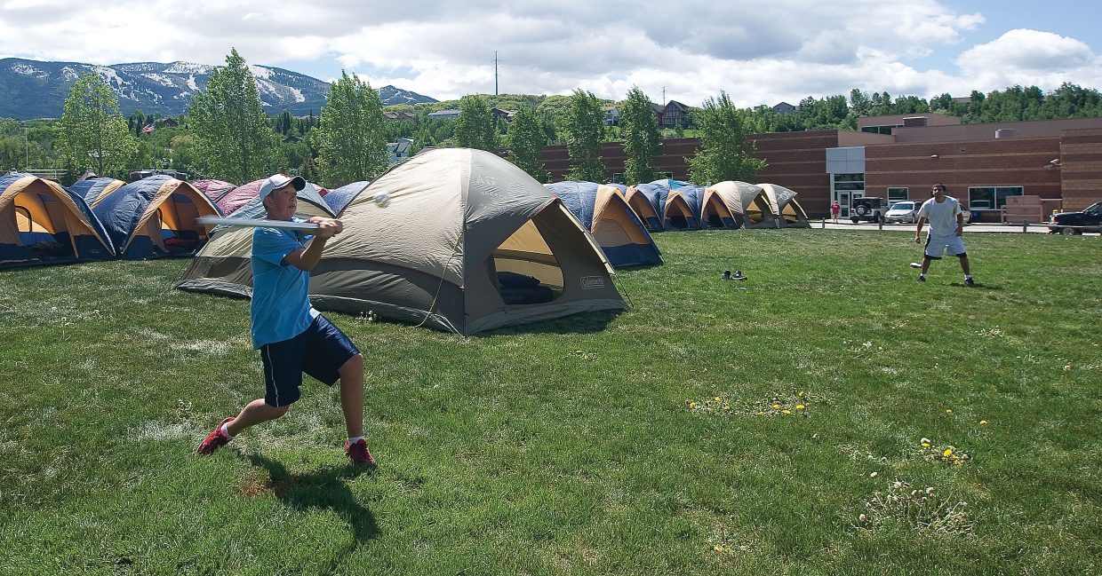 """Liam Myers, who works with the Sherpa Packer, takes a break after setting up camp in a field at the Steamboat Springs High School for a game of """"Wiffle Ball"""" with some of his co-workers Tuesday as the 2011 Ride the Rockies bike tour arrives in Steamboat Springs. The 412-mile bike tour will often call Steamboat Springs home for a few days."""