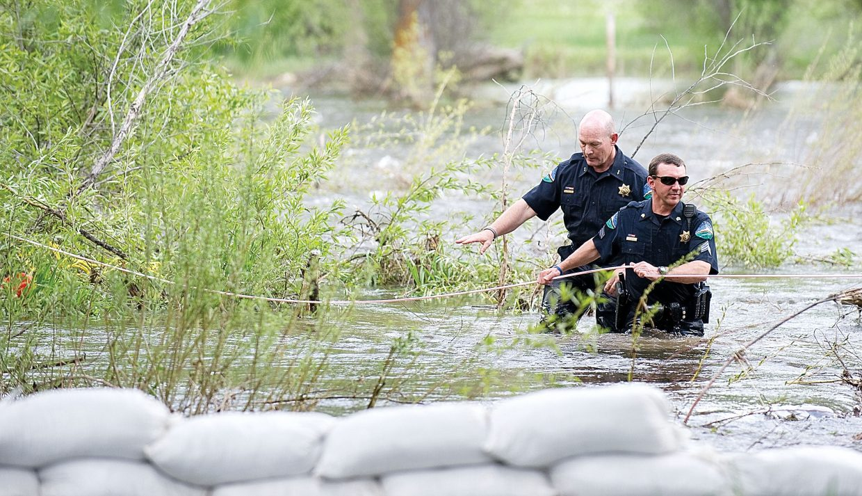 Routt County Sheriff officer Doug Scherar and Undersheriff Ray Birch work their way to she shore behind the Sleepy Bear Mobile Home Park after pulling a man from the waters of the Yampa River Wednesday afternoon. Witnesses said the man, later identified as John Christopher Noonan, fell into Soda Creek near the intersection of Lincoln Avenue and 12th Street about 4 p.m.
