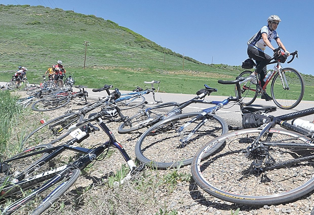 Cyclist Tina Wilbanks makes her way past a line of bikes before stopping at an aid station on Routt County Road 33 as part of Ride the Rockies.