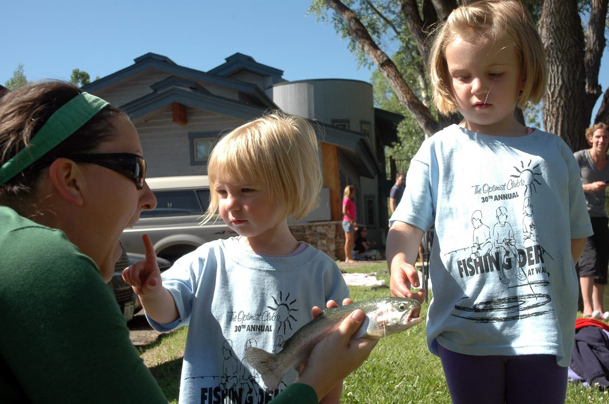 Tara Weiss shows a rainbow trout to young fishers Micah and Macee Wettlaufer, ages 1 and 4.