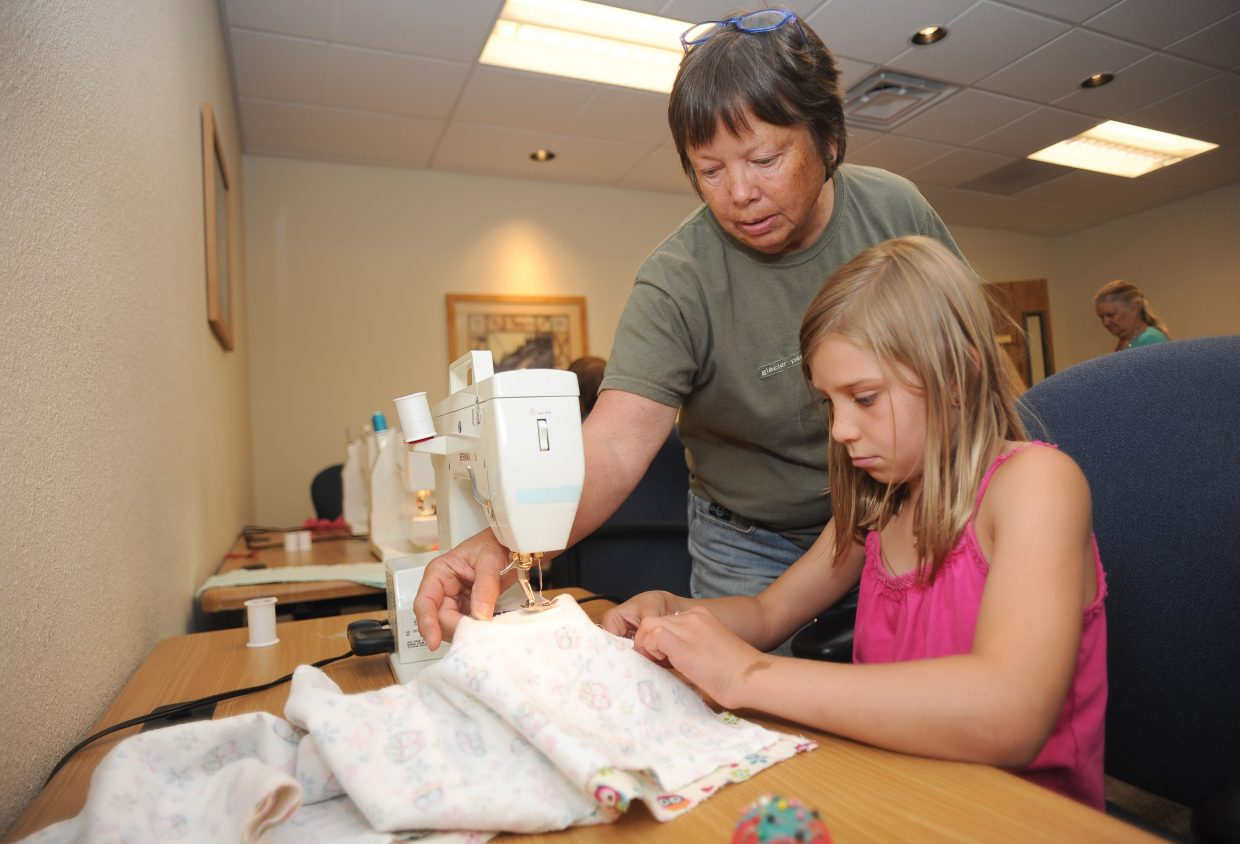 Nine-year-old Tinsley Wilkinson gets a helping hand from Barbara Cannizzo during the first day of the 4-H sewing program in one of the offices at the Routt County annex building. Children in the summerlong sewing program learn to sew their own clothing as part of the 4-H program.
