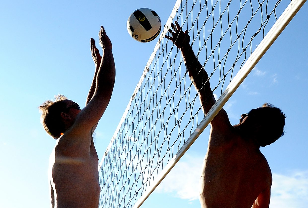 Jordan Worden, right, tips the ball over the net in front of Eric Johnston on Monday night at the sand volleyball courts at Howelsen Hill in Steamboat Springs during rec league play. Worden won the matchup, but Johnston's team, Practice Safe Sets, won the day, defeating Some Spike It Hot in two games.