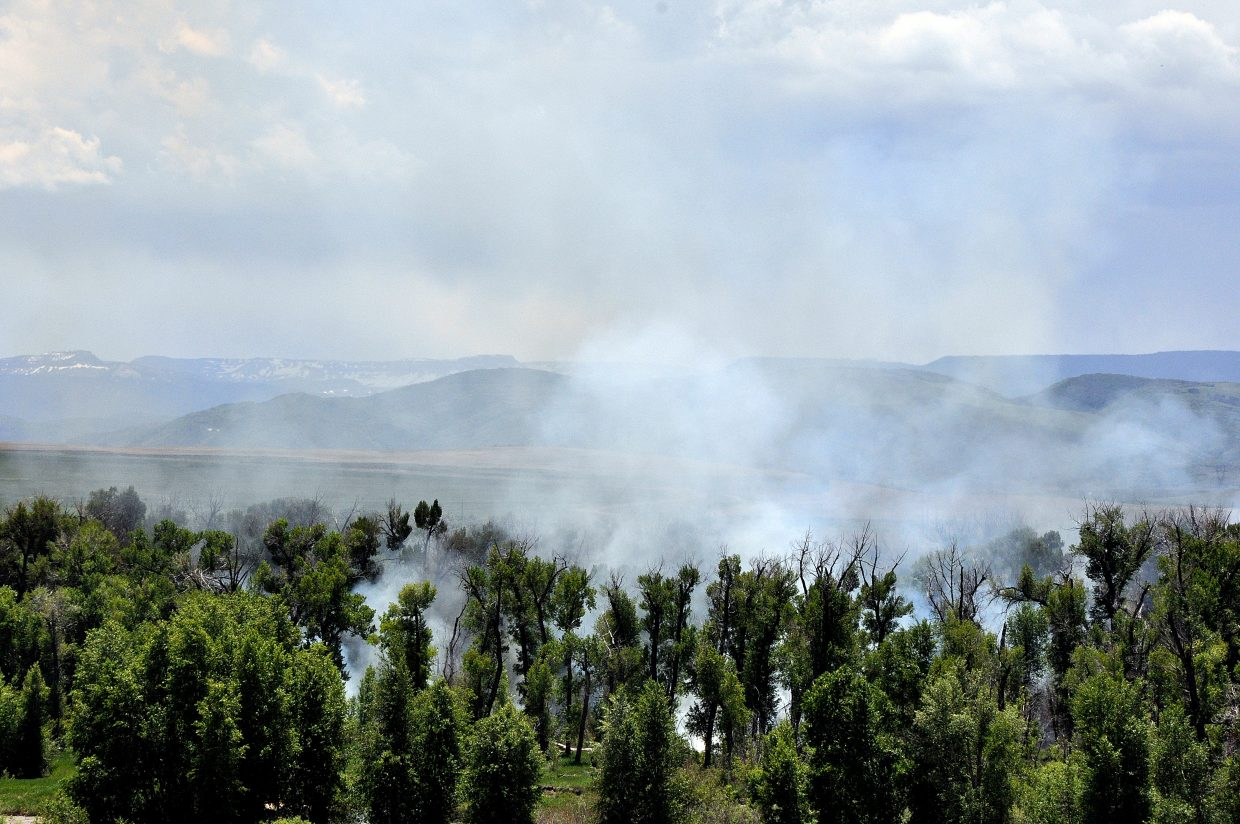 A wildfire burns Monday in the cottonwood trees at Carpenter Ranch just east of Hayden. Firefighters planned to resume fighting the fire on Tuesday morning.