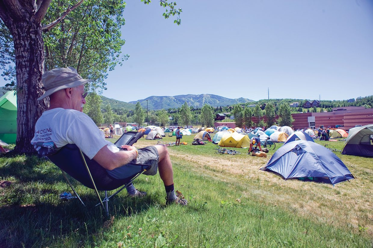 Cyclist Marty Nicholas relaxes on the lawn of the Steamboat Springs High School on Wednesday afternoon. Nicholas had just ridden from Craig to Steamboat as part of the Bicycle Tour of Colorado.