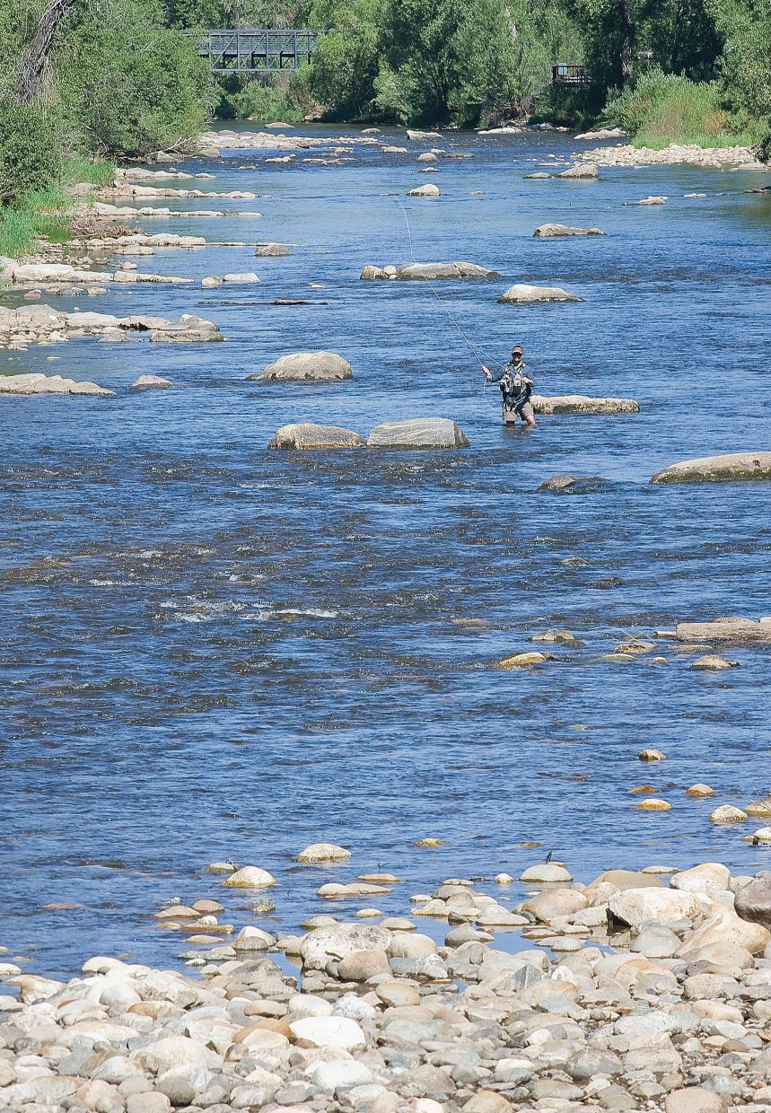 Ed Patterson, who was visiting from Boulder, fishes in the cool waters of the Yampa River on Wednesday morning. Commercial tubing on the river was stopped Wednesday after the river fell below 85 cubic feet per second. The river, however, is still supports fishing.