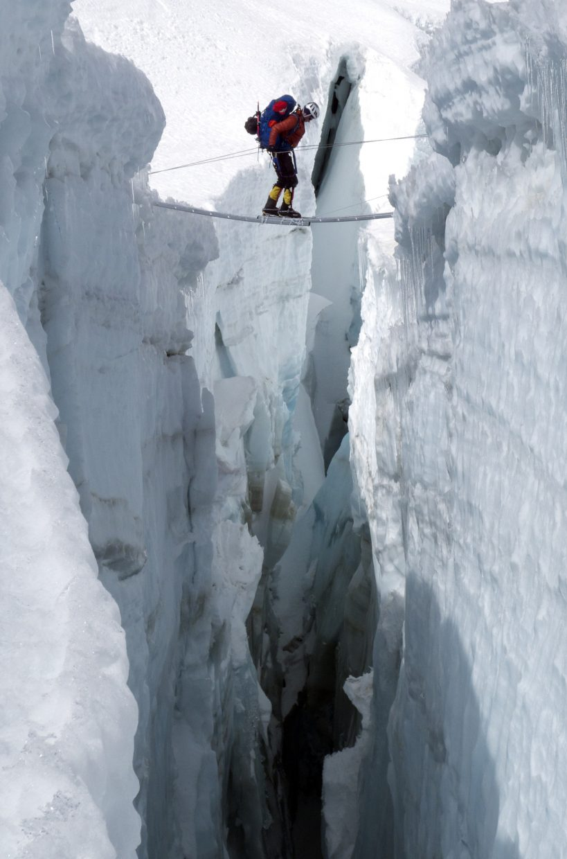 """Eric Meyer makes his way across a ladder over a crevice in the Khumbu Icefall low on Mount Everest. The Icefall is a constantly moving glacier and among the most dangerous parts of the Everest climb. Said Meyer about the crossing in the photo: """"That's as frightened as I was on the mountain."""""""