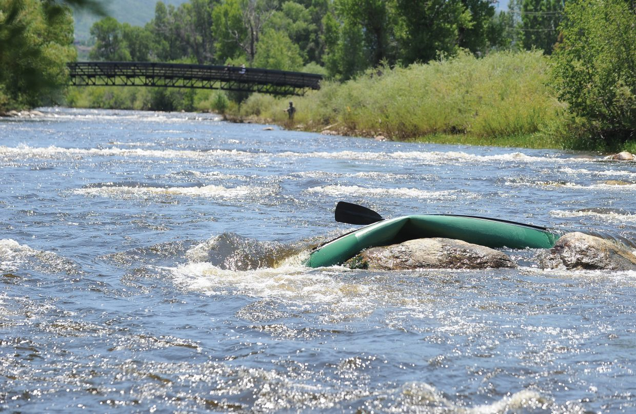 The twisted frame of a canoe is jammed on the rocks of the Yampa River just past 12th Street. The canoe's owner, John Fielding, and his son were able to swim to shore Thursday evening after the canoe tipped. Fielding said he will wait for the water to recede to safe levels before trying to recover the craft.