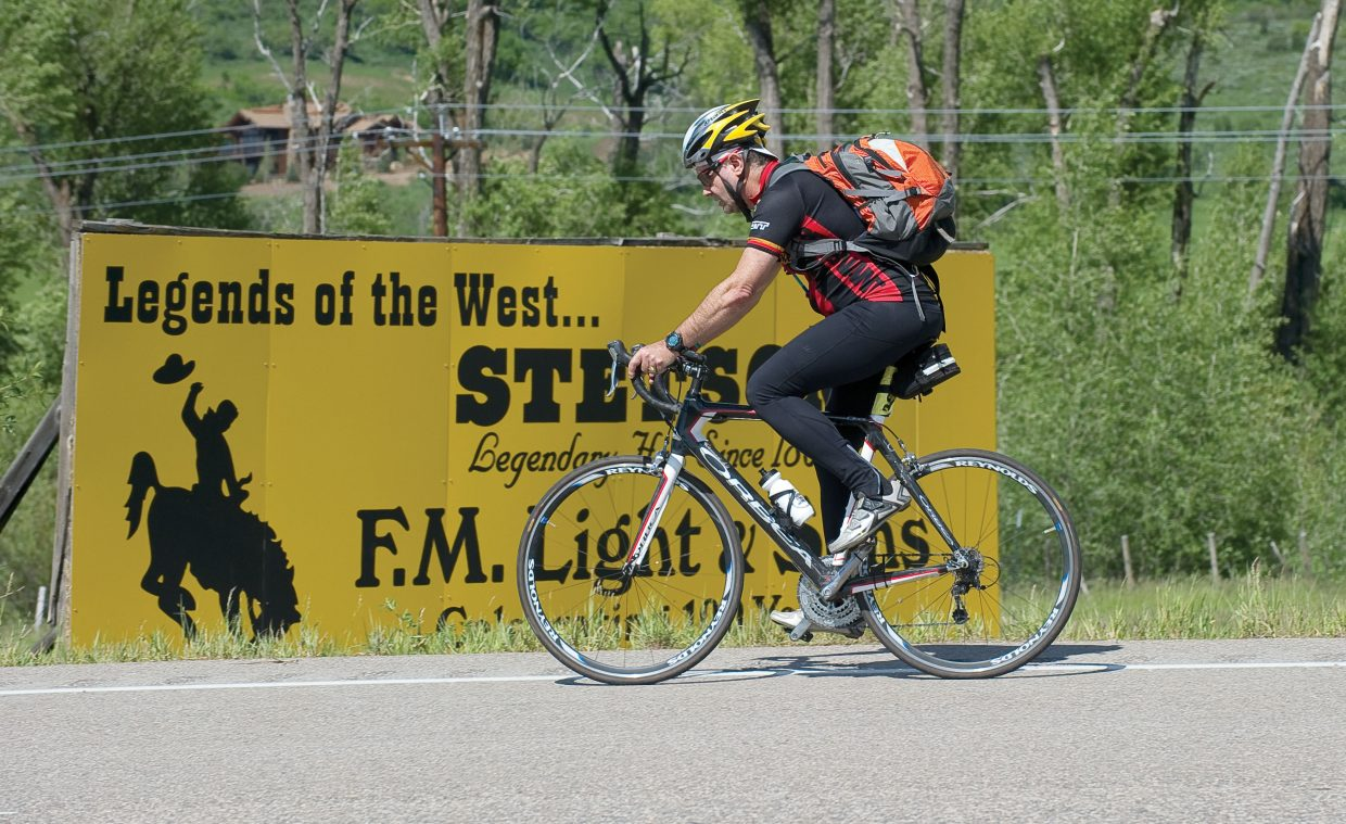 Cyclist Andy Galewsky, from Austin, Texas, rides past the F.M. Light & Sons sign on U.S. 40 during the Bike Tour of Colorado on Tuesday afternoon. The cyclists in the tour made the 80-mile journey from Granby over Rabbit Ears Pass and into Steamboat Springs on Tuesday. On Wednesday they will head to Glenwood Springs.