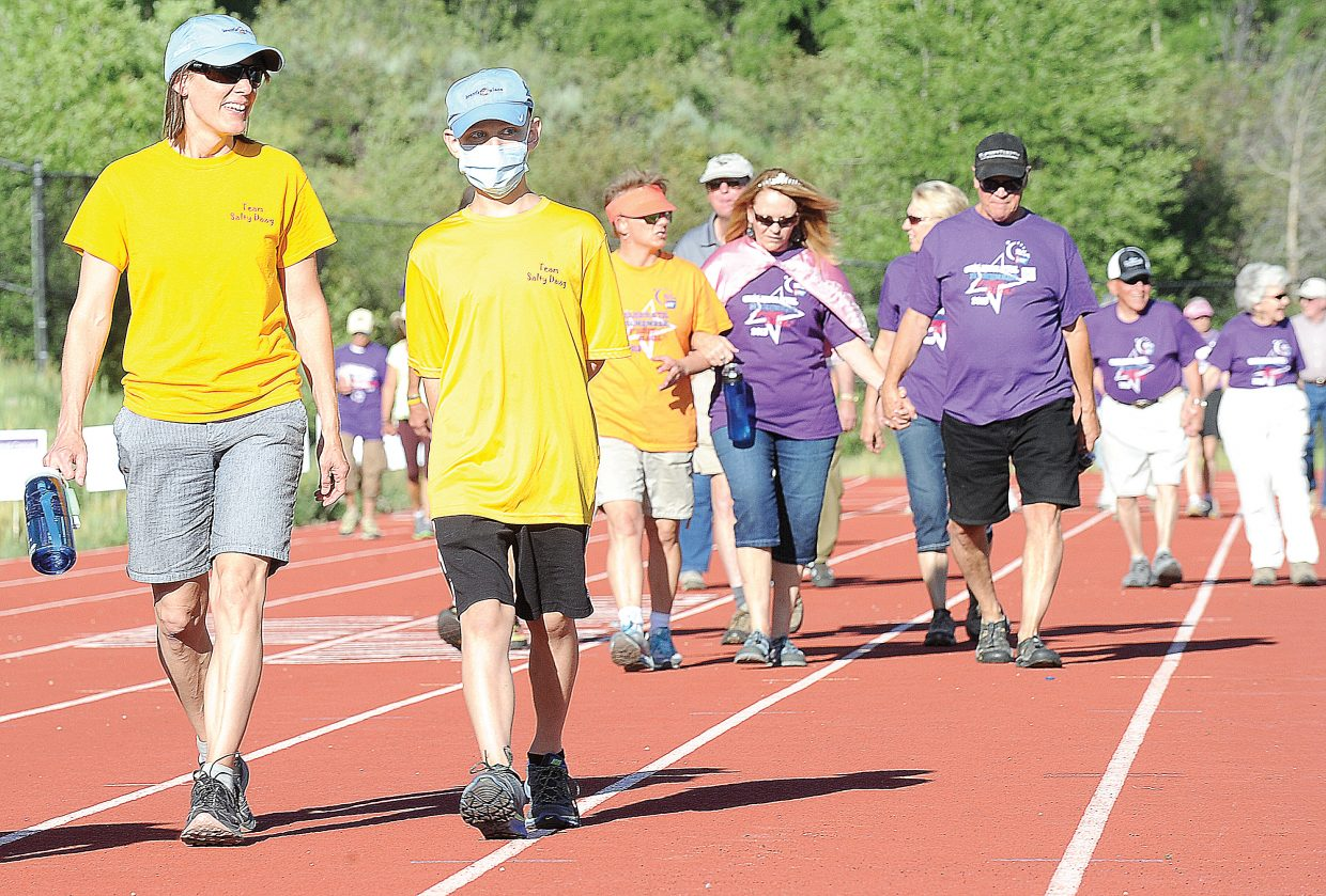 Lisa Kinnison and her son Izaac walk around the track during the Relay For Life fundraising event Friday evening at Steamboat Springs High School. Izaac, 11, was diagnosed with a malignant tumor in his brain a year ago. He underwent treatment and recovered but learned earlier this spring that the tumor has returned. He has spent the past several months in Denver undergoing more treatments but was able to return to Steamboat Springs on Friday evening to walk, and inspire those around him, during the annual Relay For Life.