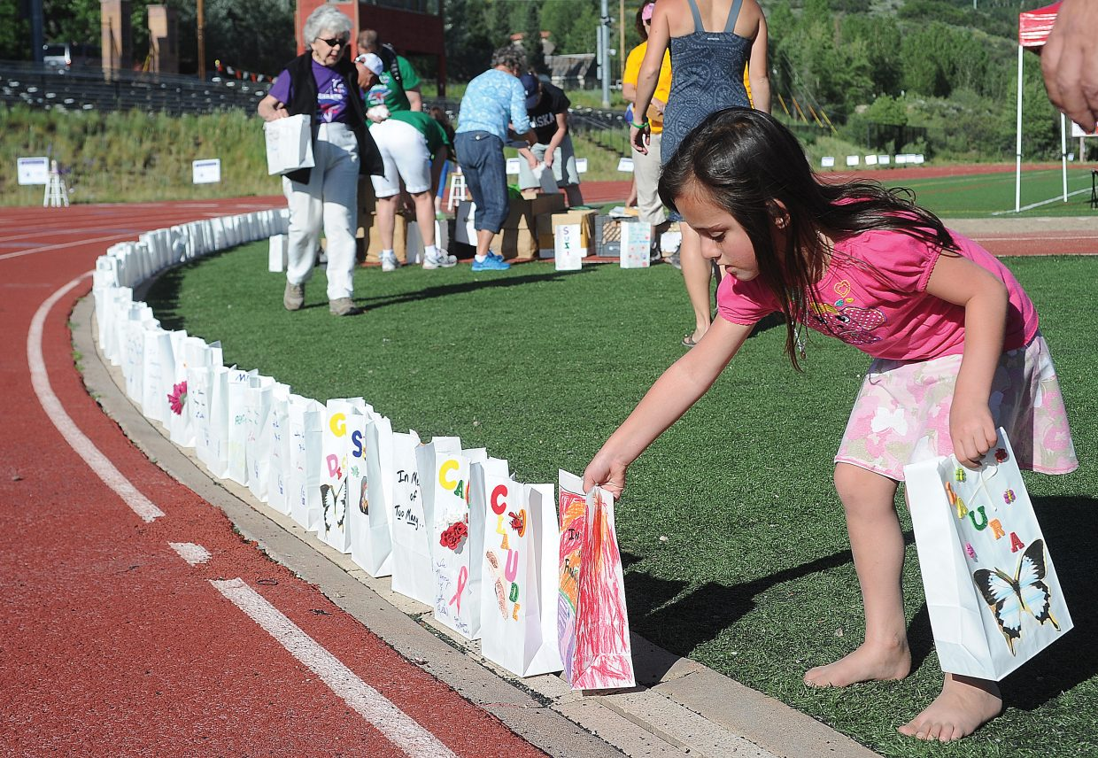 Jordan Latrimurti places luminaries around the Steamboat Springs High School track Friday evening as part of the annual Relay For Life fundraiser. The money raised goes to the American Cancer Society.
