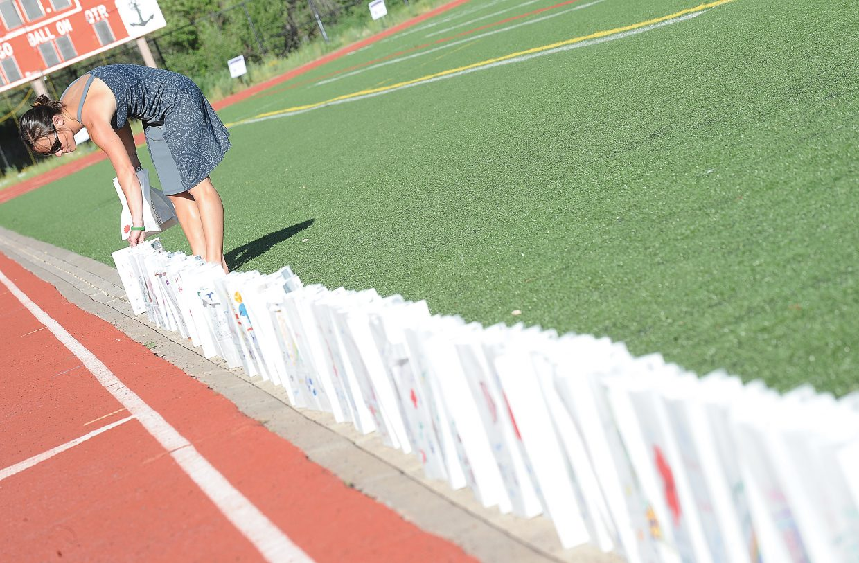Missy Detzner places luminaries around the Steamboat Springs High School track Friday evening as part of the annual Relay For Life fundraiser. The money raised from the event goes to the American Cancer Society.