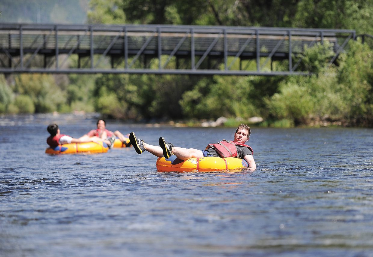 Visitor Robert Lott, front, along with friends Kevin and Chris Boddy float down the Yampa River on Friday afternoon. The Yampa fell below 700 cfs Wednesday, allowing commercial tubing. However, officials warn tubers that life vests and proper shoes should be used.