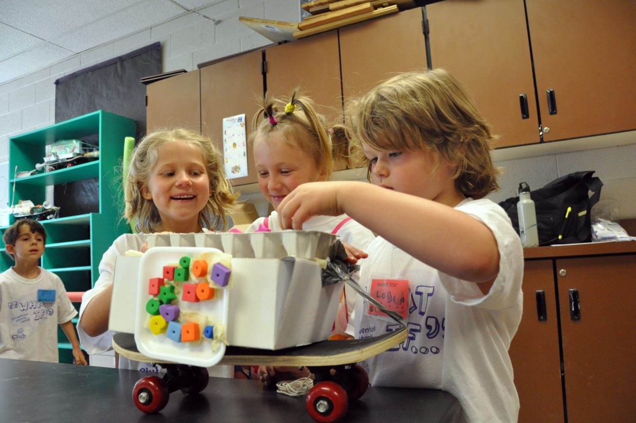 """First graders, from left, Mia Mcnamara, Audra Gowdy, and Logan Truelove admire the """"landslide"""" they built Wednesday at Camp Invention at Strawberry Park Elementary School. They will race their mini-skateboard through an obstacle course later this week to test its durability."""
