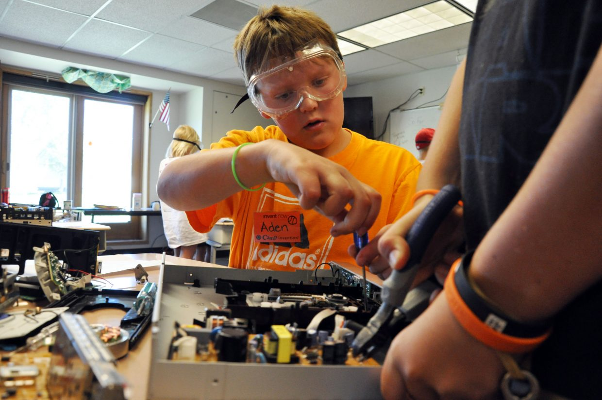 Aden Knaus, 10, removes parts from a DVD player Wednesday at Camp Invention at Strawberry Park Elementary School. Aden used the parts from the old appliance to start making a marble machine.