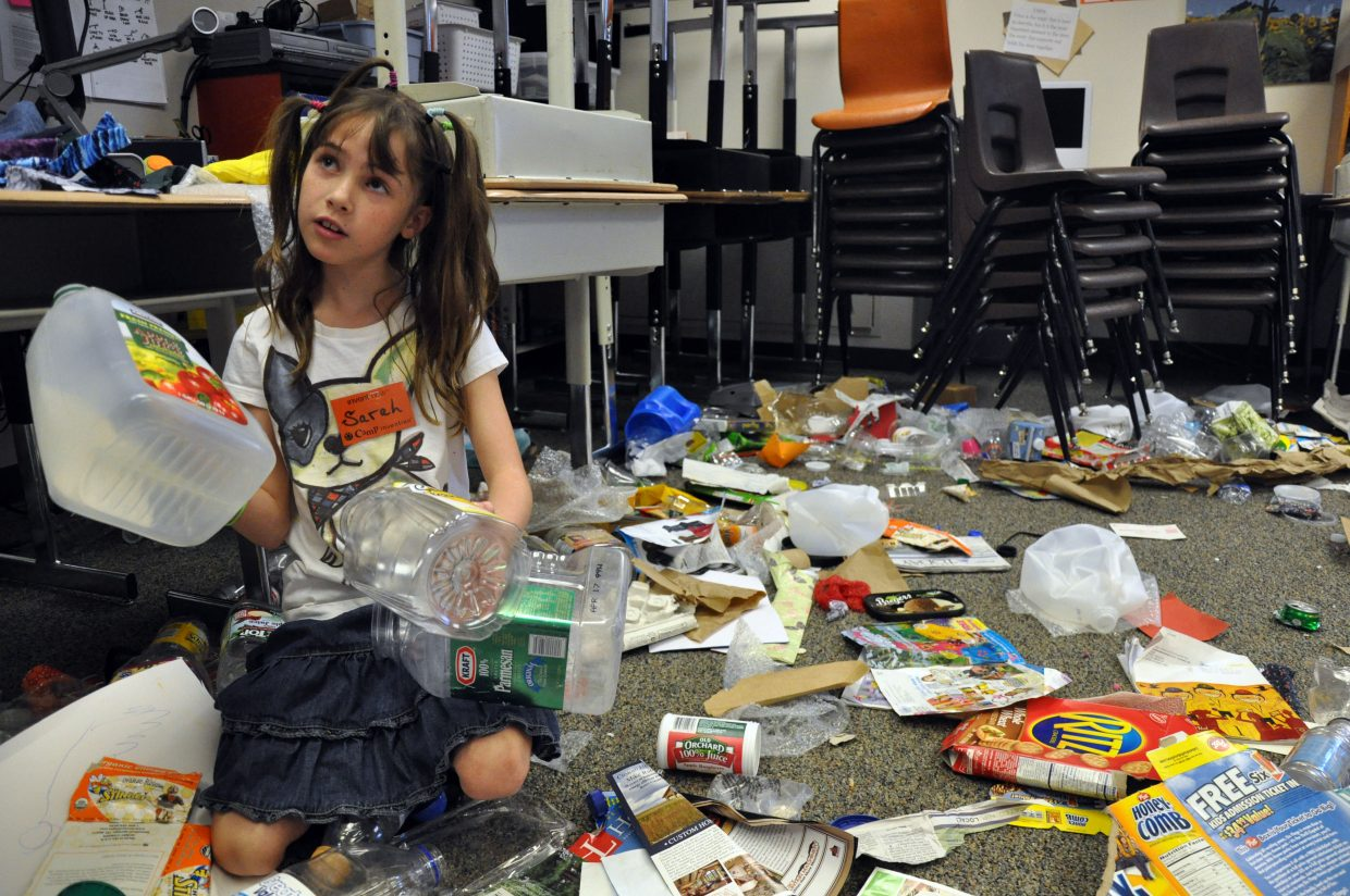 Sarah Wittemyer, 9, gathers recyclable items Wednesday that she will use to build a gumball machine at Camp Invention.