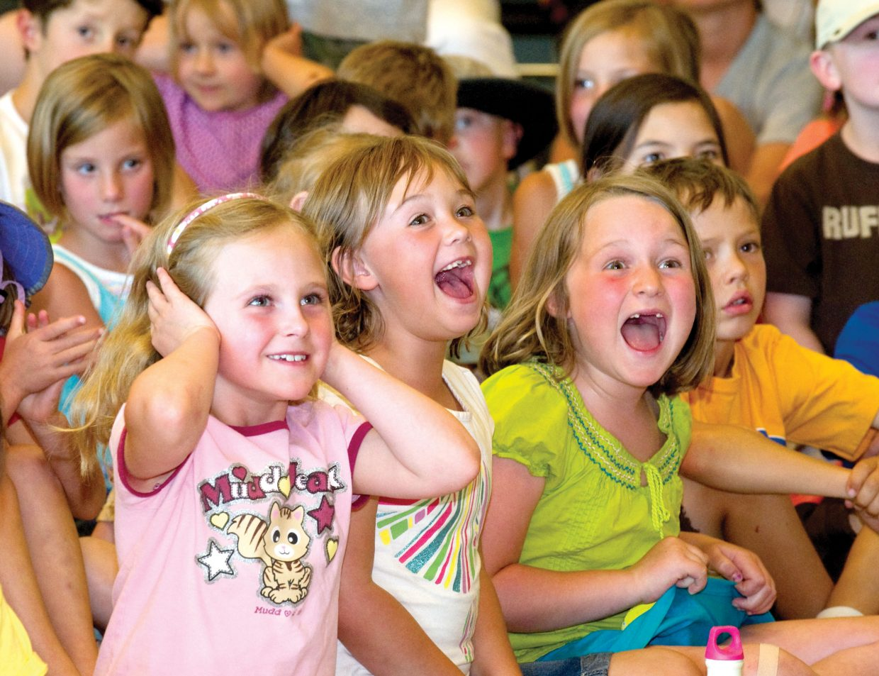 Students, from left, Sofia Karch, Paige Watson and Liv Mason react during a magic, juggling and comedy show by Ann Lincoln at the Bud Werner Memorial Library on Wednesday afternoon. The free show is part of the Youth Services Department's One World, Many Stories summer reading program.