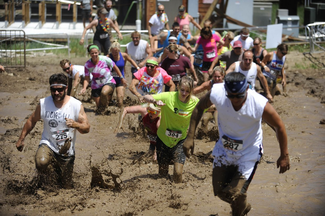 Participants run through a mud pit during the Steamboat Mad Mud Run on Saturday at Steamboat Ski Area.