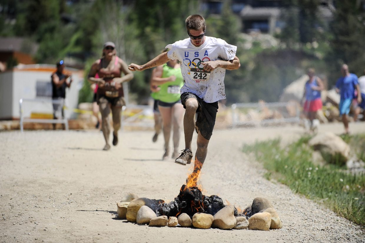 Steamboat Springs resident Eddie Marovich runs over fire near the finish of the Steamboat Mad Mud Run on Saturday at Steamboat Ski Area.