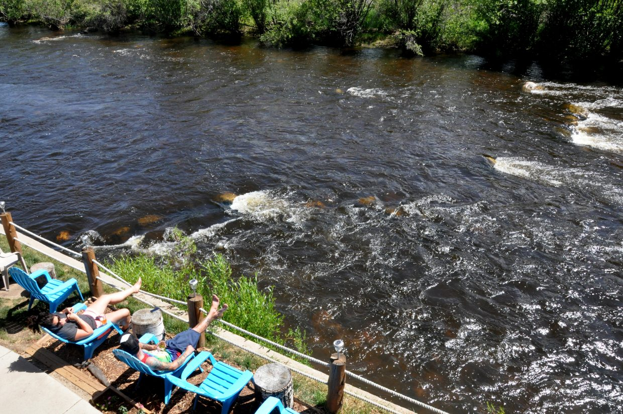 Sunbathers enjoy drinks at The Boathouse Pub on Thursday along the Yampa River. The Yampa River promenade would add several new riverfront parks to the street and make it more pedestrian friendly.
