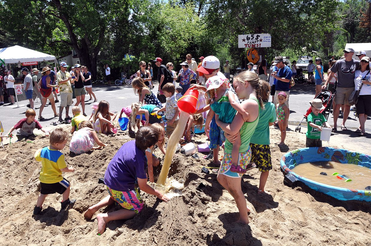 Children and parents converged on a pile of sand on Sunday in the middle of Yampa Street. The first Yampa Street Live event featured a beach theme.