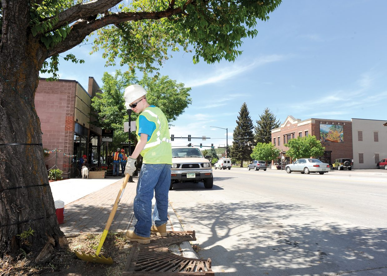 Liam McCormick cleans up around the trees that line Lincoln Avenue on Monday afternoon while working for the Community Youth Corps. The group works on various community projects and is part of a cooperative effort between the city of Steamboat Springs and the Rocky Mountain Youth Corps.